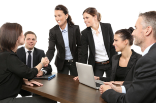 A group of business men and women attend a meeting.