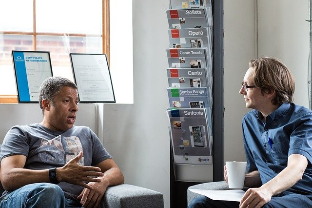 Two people having an informal meeting, with one person listening