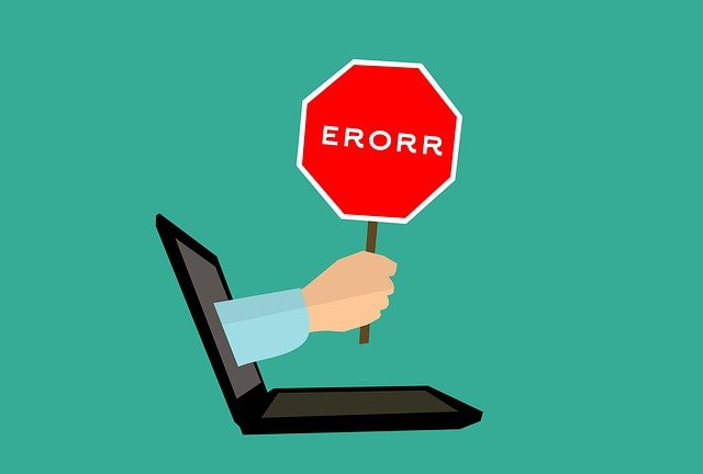 """Hand holding an """"error"""" sign, sticking out of a laptop."""