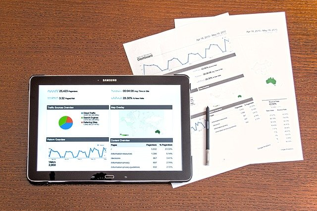Tablet and printed pages showing various graphs.